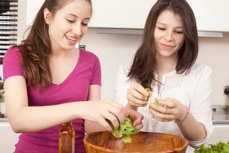 teenage girls preparing salad in kitchen Reklamní fotografie