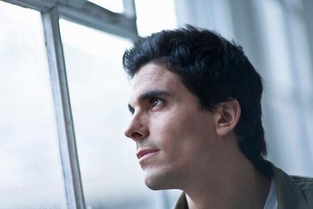man Looking through the window Imagens