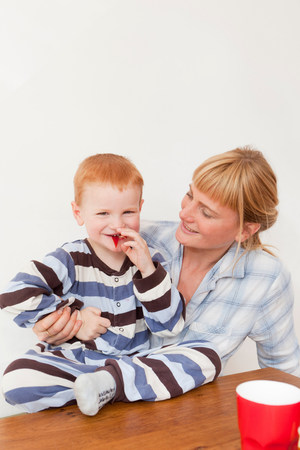 Mother and son in pajamas at table Stock Photo