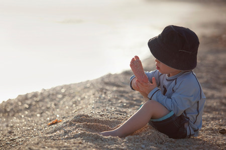 Toddler boy playing with sand on beach Stock Photo