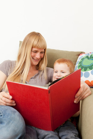 Mother and son reading together on sofa