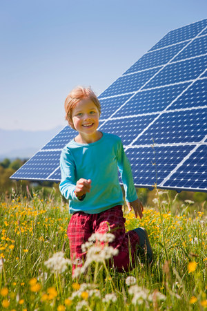 Boy playing in field by solar panel