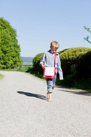 Boy walking barefoot on rural road