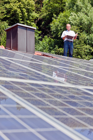 Man standing on solar paneled roof