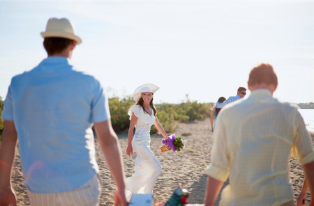 Bride walking with friends on beach