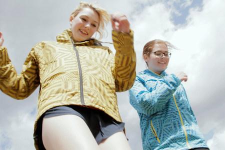 Girls in parkas walking against blue sky 免版税图像