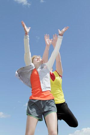 Girls jumping for joy against blue sky Stock Photo