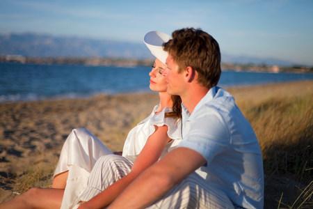 Newlywed couple sitting on beach Reklamní fotografie