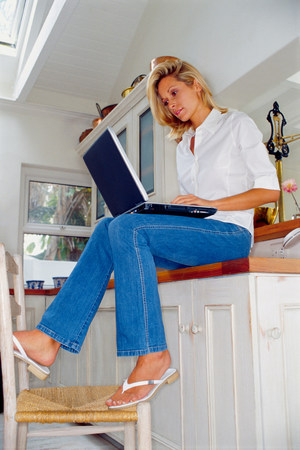 Woman using laptop in kitchen 스톡 콘텐츠