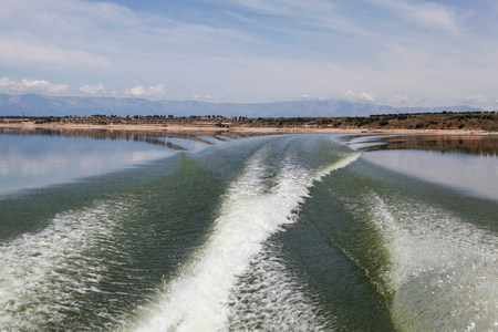 Waves behind speedboat in lake