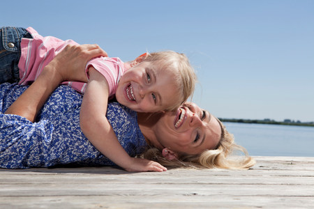 Mother and daughter playing on dock Archivio Fotografico