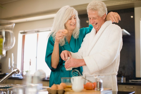 Older couple in bathrobes cooking