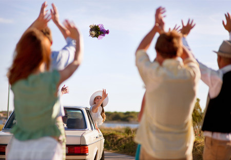 Bride throwing bouquet from car