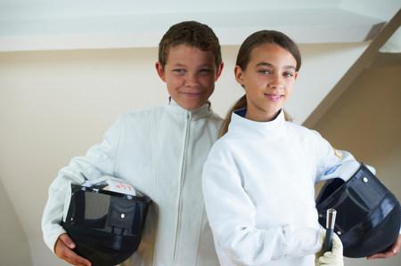 Children wearing fencing costumes