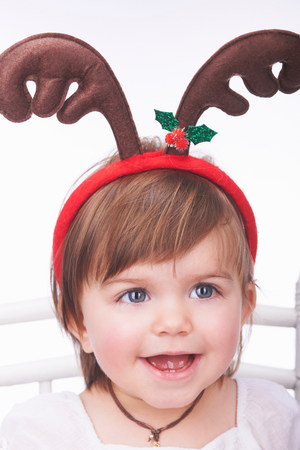 Baby girl wearing reindeer antlers Stockfoto