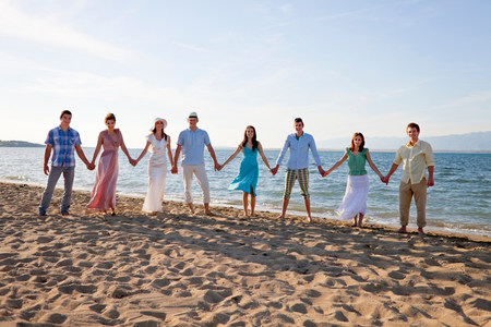 People standing hand-in-hand on beach Reklamní fotografie