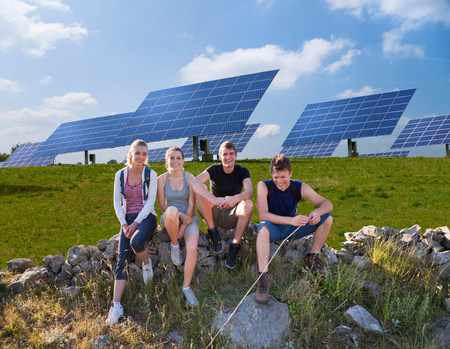 People sitting on wall by solar panels