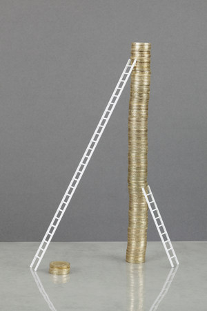 Ladders leaning on stack of coins Banco de Imagens