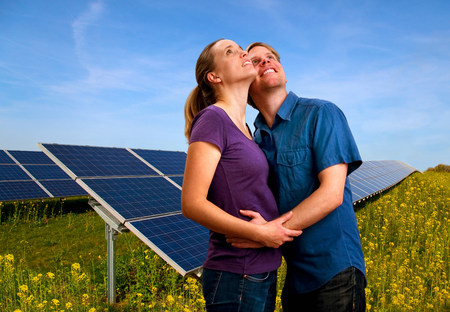Couple hugging by solar panels