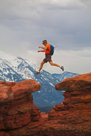 Hiker jumping between rocks Stock Photo