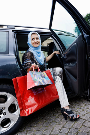 Woman in headscarf with shopping bags Stock Photo