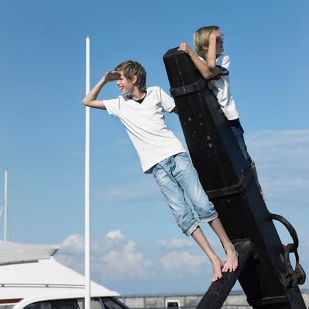 Boys climbing on pier