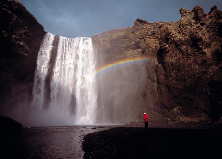 Waterfall over rocky cliffs with rainbow