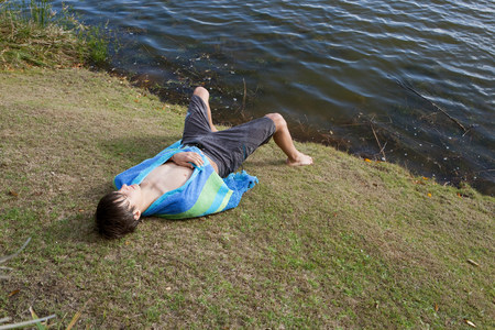 Teenage boy laying on riverbank Foto de archivo