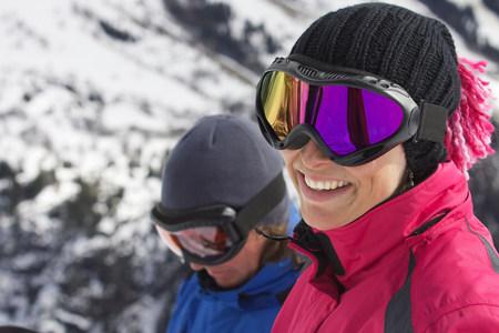 Smiling woman wearing ski goggles Stock Photo