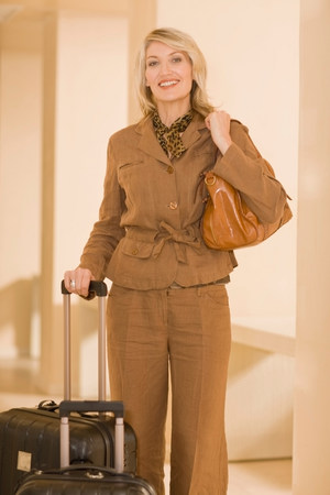 Smiling businesswoman rolling luggage