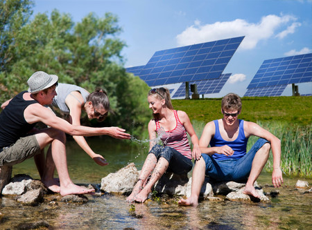 People sitting in river by solar panels Stock Photo