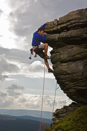 Rock climber scaling steep rock face Stock Photo