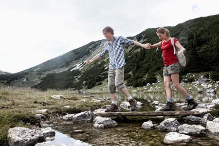 Couple traversing rocky creek Stock Photo