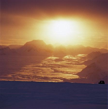 SUV driving over snow-covered glacier Фото со стока