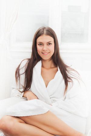 Smiling woman wearing bathrobe Imagens