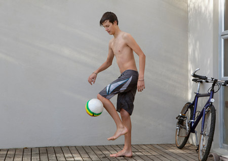 Teenage boy playing with soccer ball