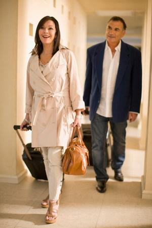 Older couple rolling luggage in walkway