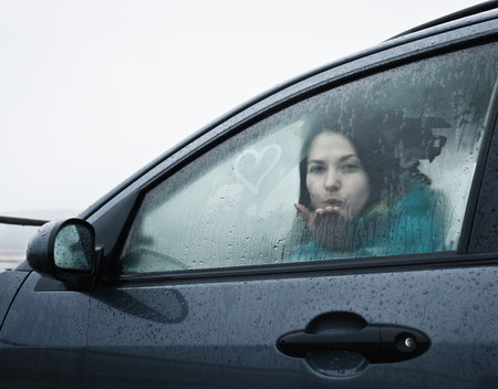 Teenage girl blowing kiss from car