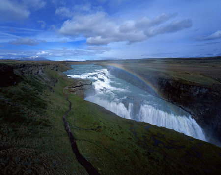 Rainbow over cliffs and waterfall