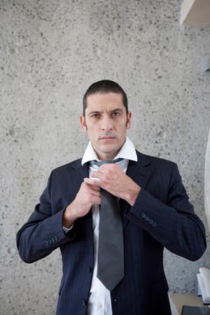 Businessman tying his tie Stock Photo