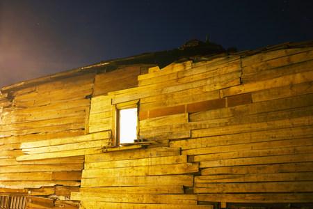 Lit window of wooden building Stock Photo