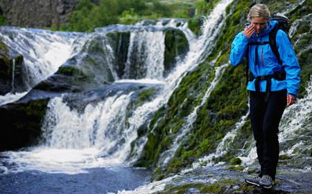 Hiker walking over river on mountainside
