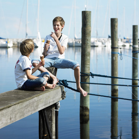 Boys eating ice cream on pier Imagens