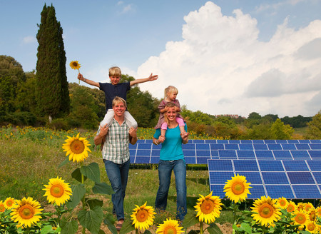 Family in field by solar panels