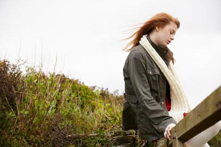 Teenage girl sitting on wooden fence Imagens