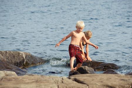 Children climbing on rocks by lake