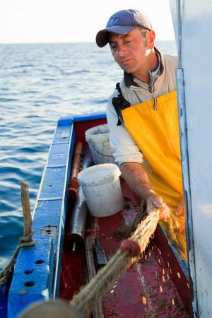 Fisherman reeling in nets on boat 版權商用圖片