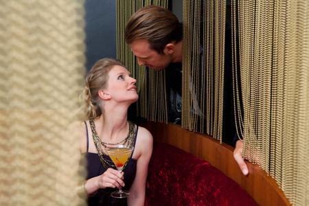 Couple talking through curtain in bar
