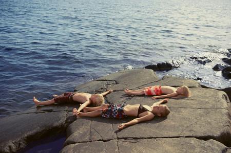 Children laying on rocks by lake