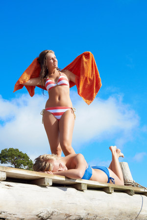Teenage girls in swimsuits drying off